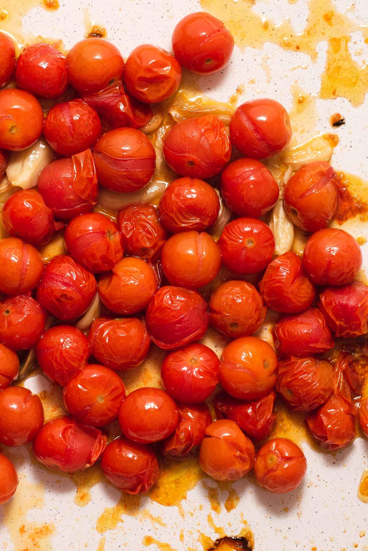 Close up of shriveled roasted cherry tomatoes on white background