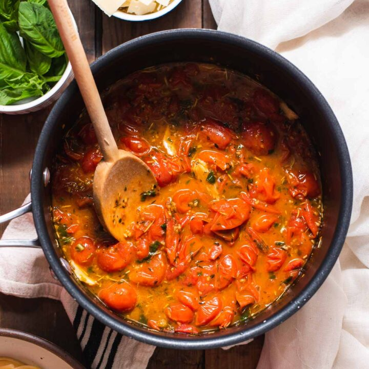 Cherry tomato sauce with wooden spoon in a black sauce pot