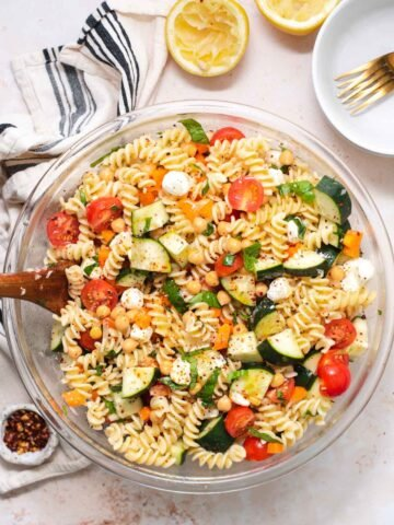 Overhead view of large glass bowl filled with pasta salad