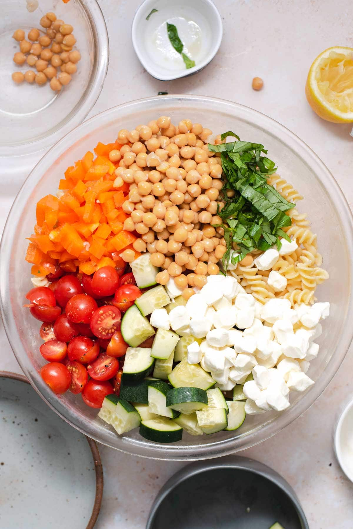 Pasta salad ingredients portioned out into large glass bowl