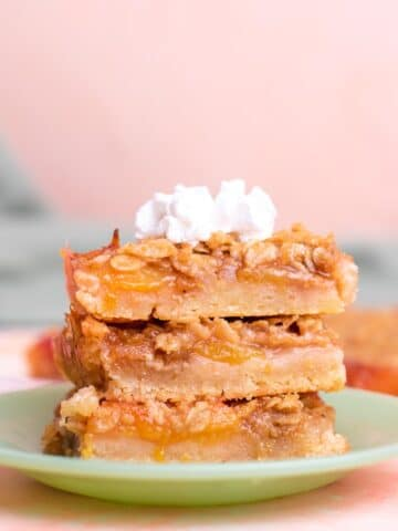 Three peach bars stacked on top of each other with a dollop of whipped cream on top