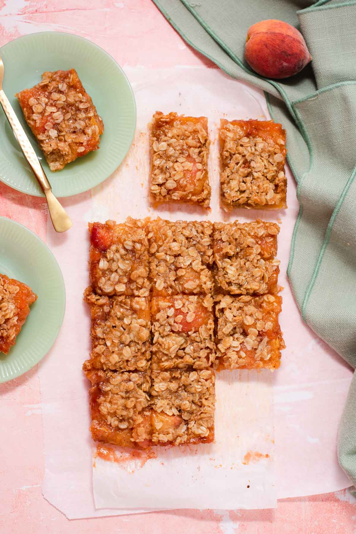 Overhead view of 12 peach bars sliced and scattered on a pink background and jadeite plates