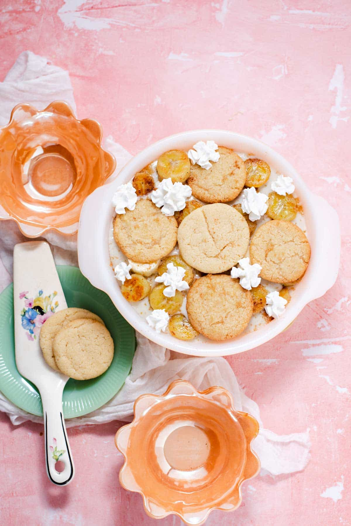 Overhead view of bowl of banana pudding next to orange and green plates on a pink background