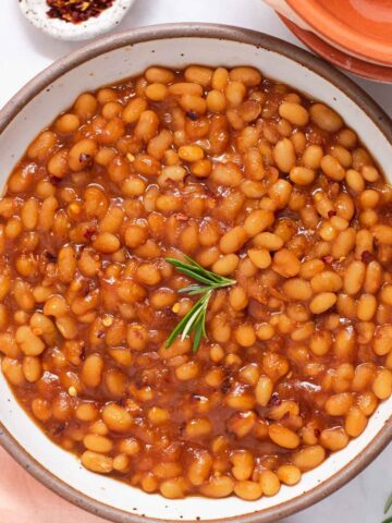 Close up of orange-brown baked beans with a sprig of rosemary on top in a white bowl