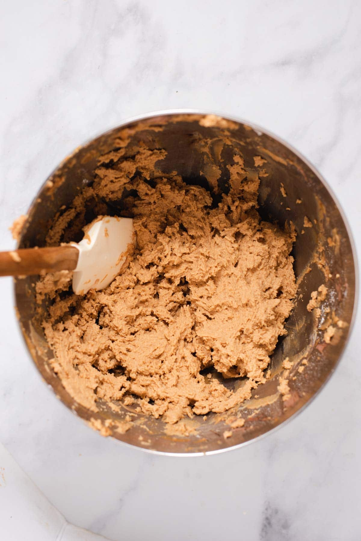 Overhead view of mixing bowl filled with peanut butter filling and white spatula