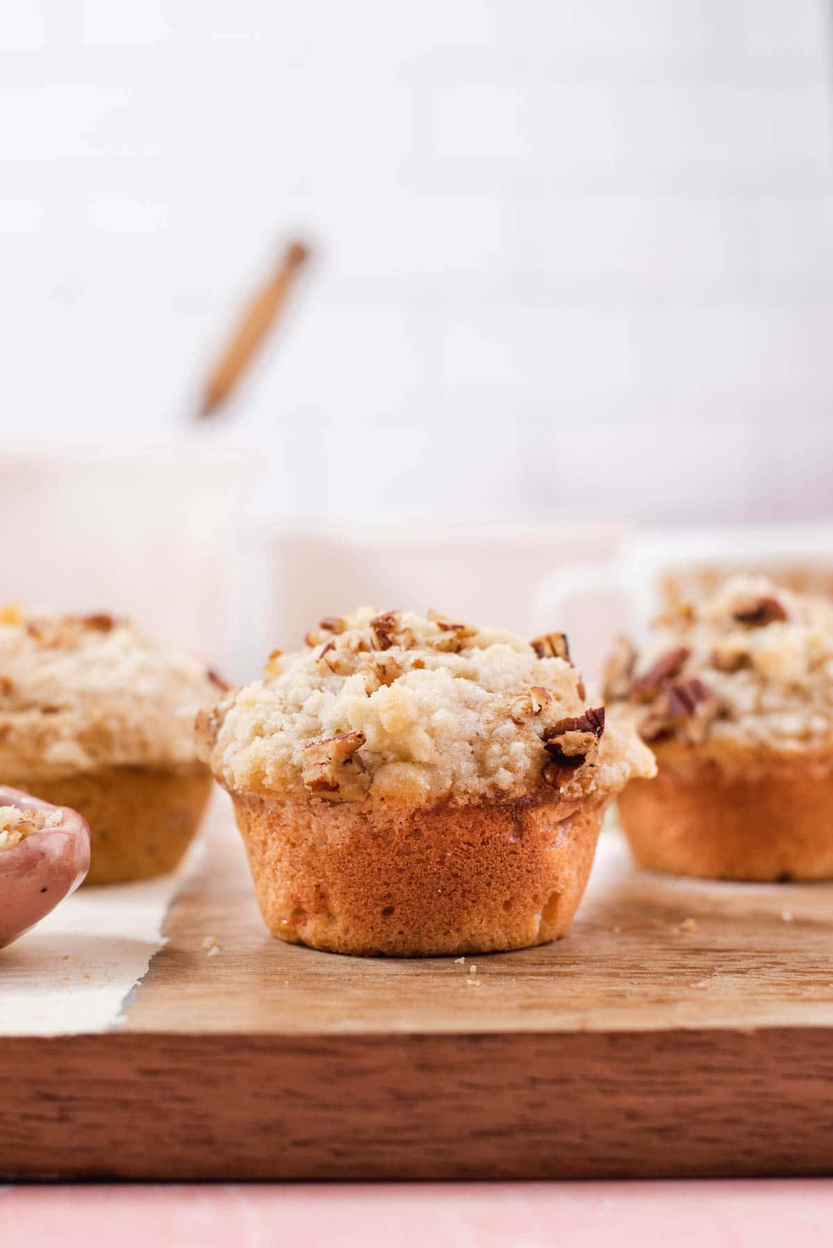 Muffin with crumb topping with two more muffins in the background