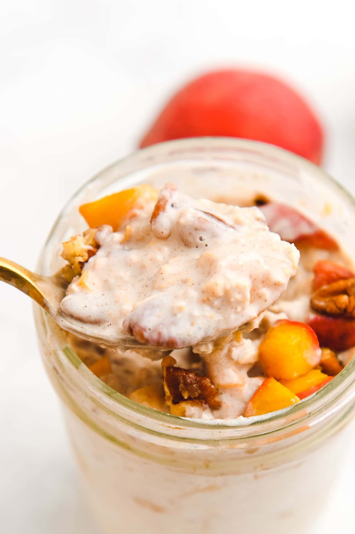 Gold spoon lifting a bite of overnight oats out of a glass jar