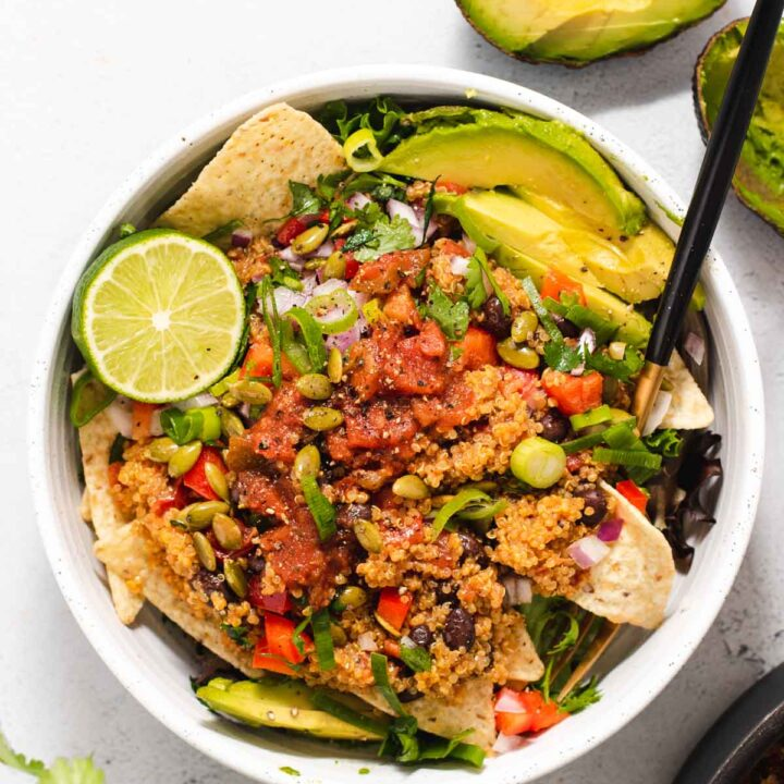 Overhead view of large white bowl filled with quinoa salad, avocado and a life half