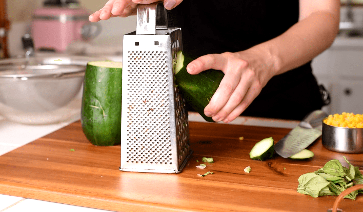 Large zucchini being shredded on a metal box grater on a wooden cutting board