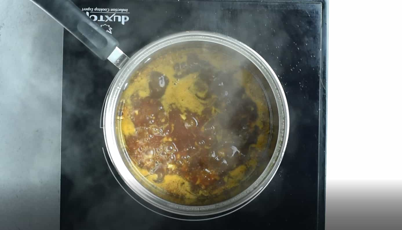 Overhead view of simmering sauce in a sauce pot on black stove top