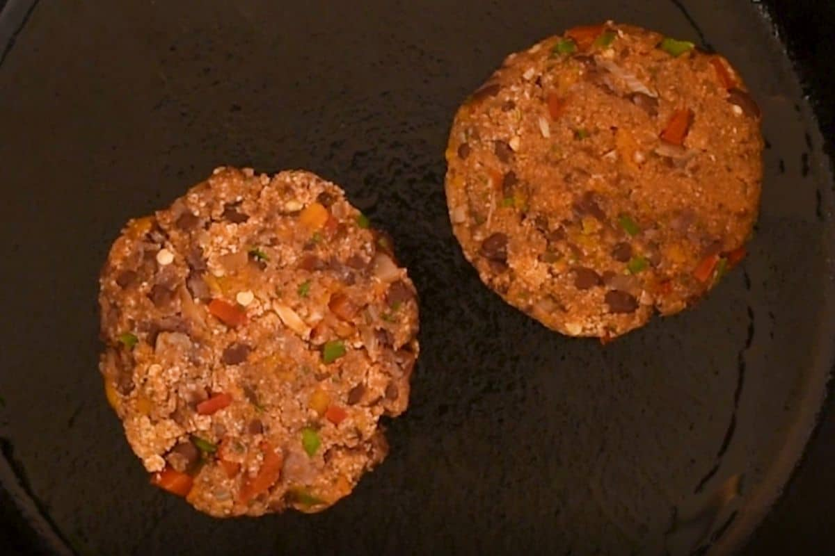 Close up of two black bean patties on a black cast iron skillet