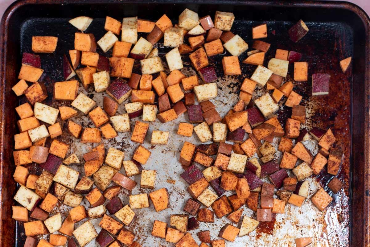 Small white and orange sweet potato pieces on a sheet pan