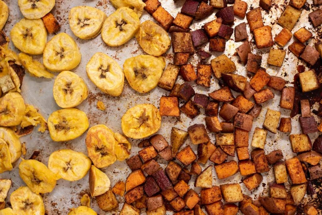 Close up of roasted sweet potato and plantains on a sheet pan
