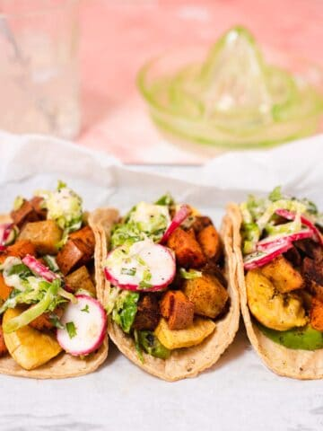 Close up of three sweet potato tacos in corn tortillas with a green lime juicer in the background