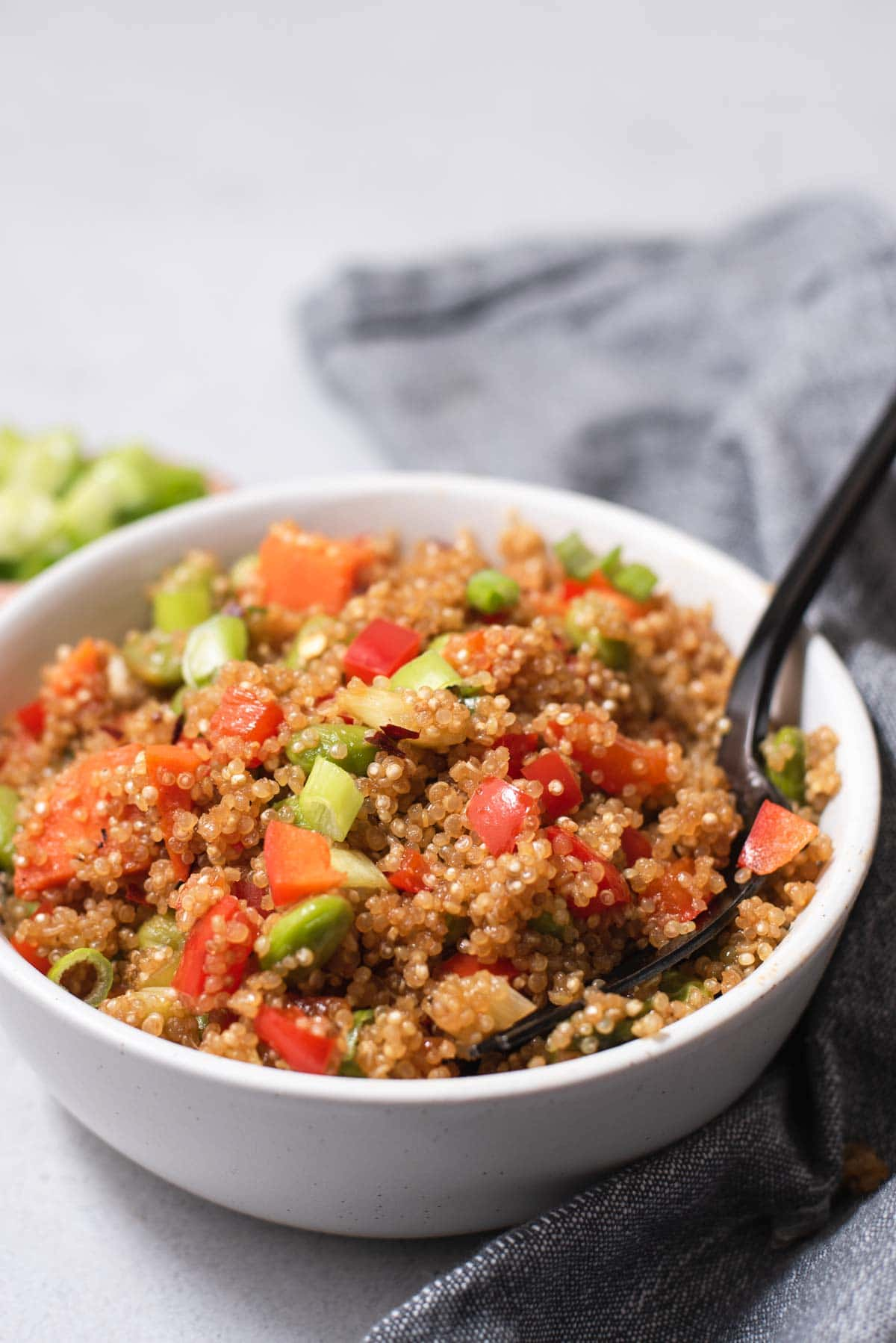 Black fork in a white bowl filled with quinoa fried rice