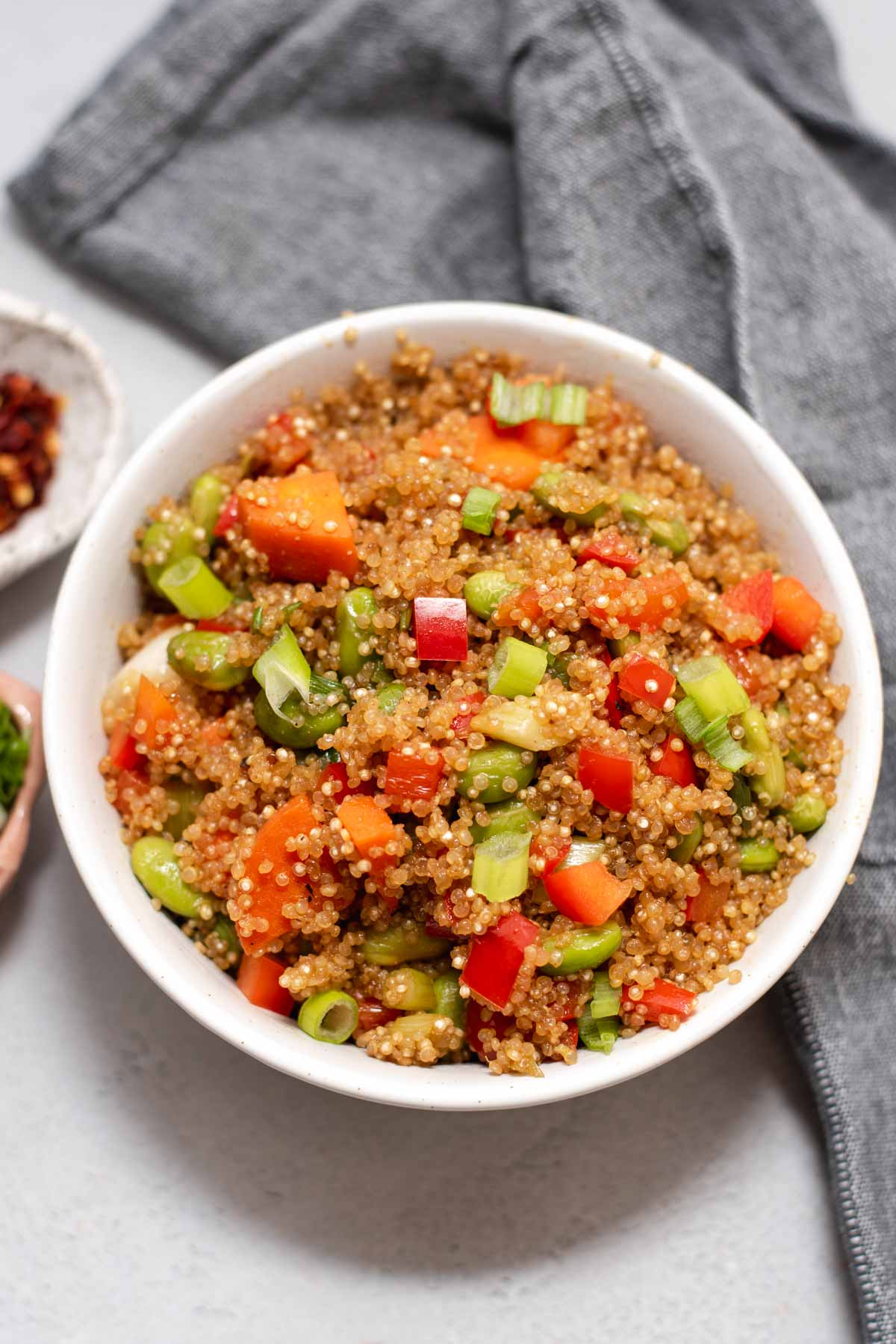 Overhead view of white bowl filled with quinoa fried rice on a gray background