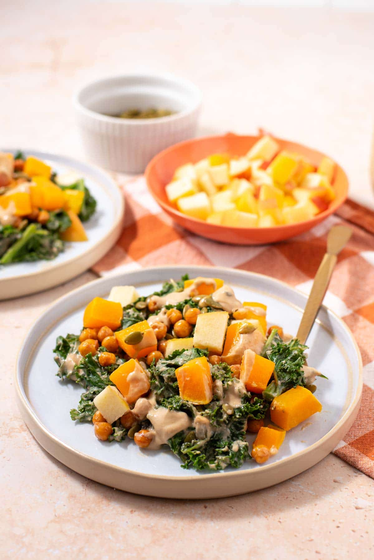 Kale and butternut squash salad on a white plate with bowl of sliced apple in the background