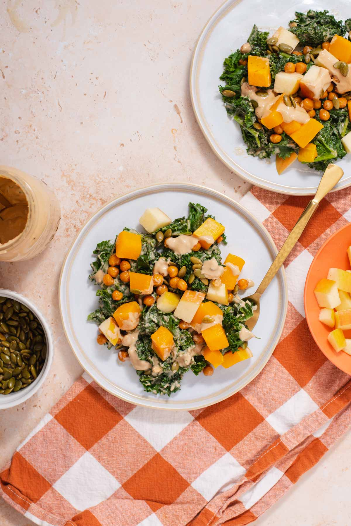 Overhead view of white plate with kale salad on an orange checked cloth