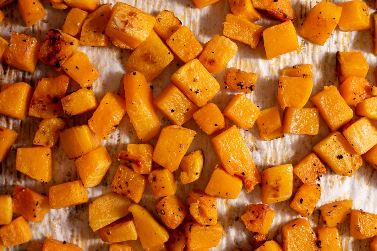 Diced butternut squash on parchment paper after being roasted