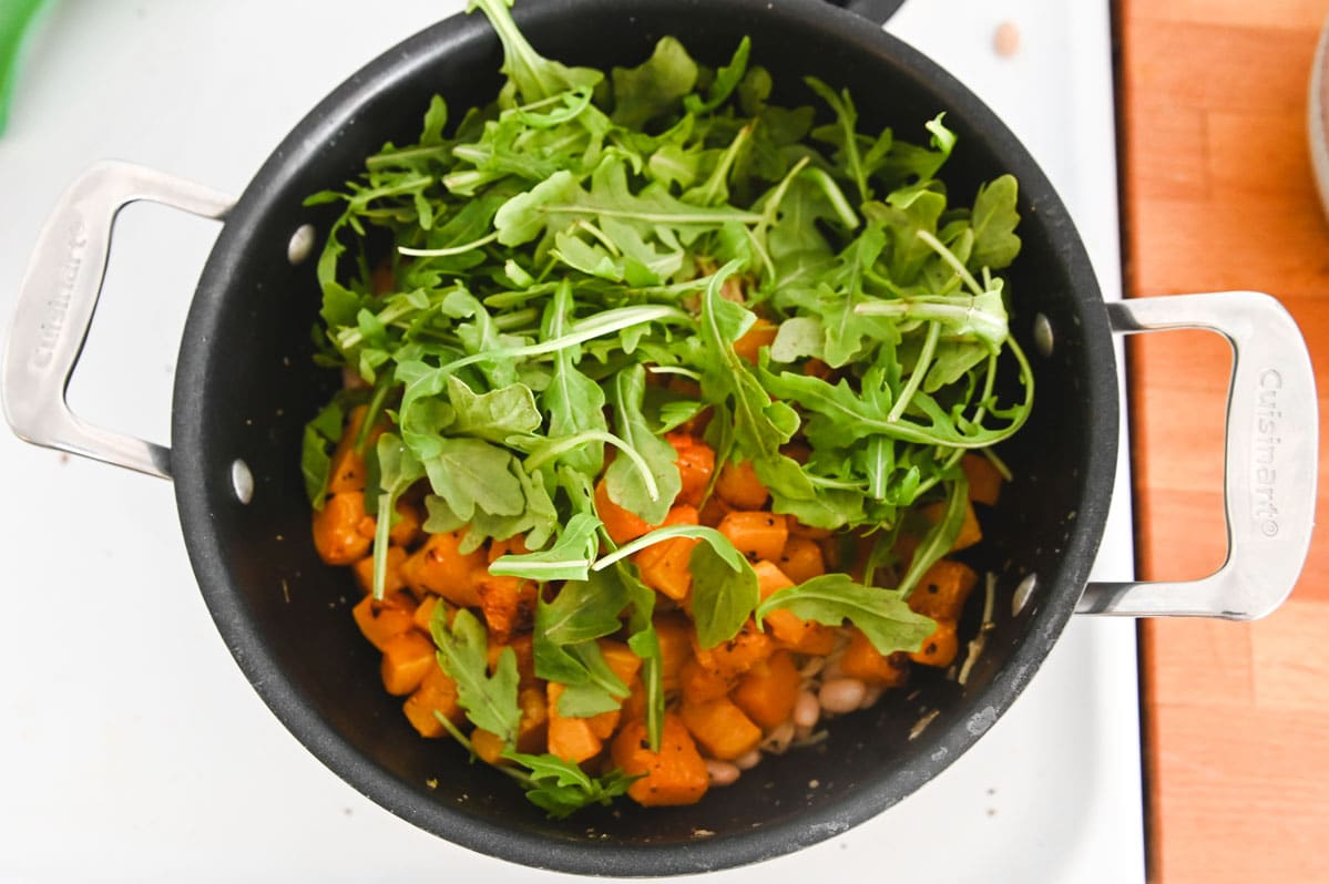 Overhead view of black Dutch oven with arugula and butternut squash inside