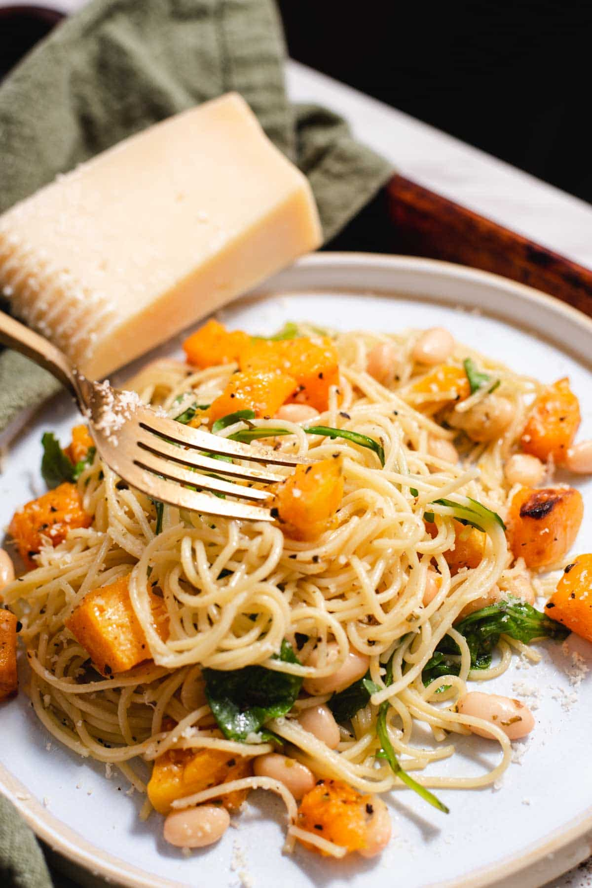 Gold fork twirling angel hair pasta and butternut squash