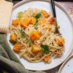 Overhead view of white plate with pile of angel hair pasta and butternut squash