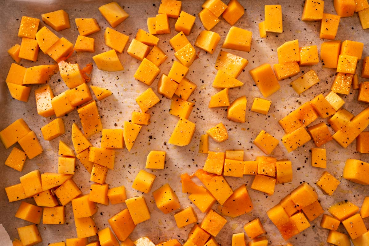 Diced butternut squash on parchment paper before being roasted