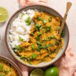 Overhead view of red lentil curry in a white bowl next to limes