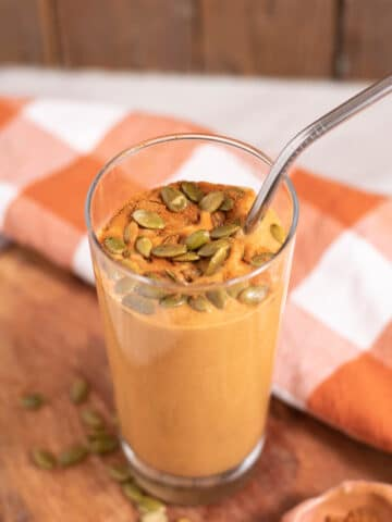 Tall glass of orange smoothie topped with pumpkin seeds and cinnamon on a wood and orange checked background