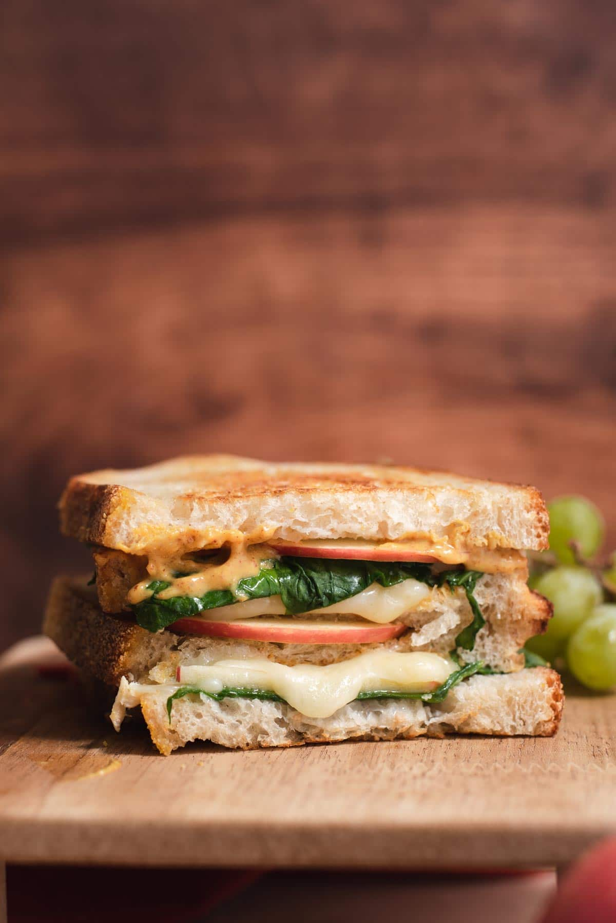 Two stacks of grilled cheese, apple and spinach on a wood tabl