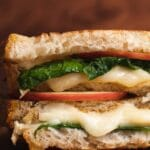 Close up of double layered sandwich with spinach, melting cheese and apple slices