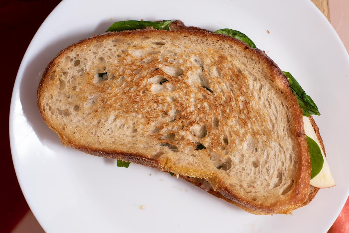 Golden toasted sourdough sandwich on a white plate