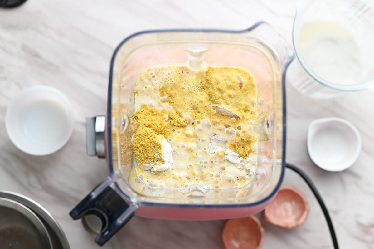 Blender filled with ingredients used to make vegan cheese sauce