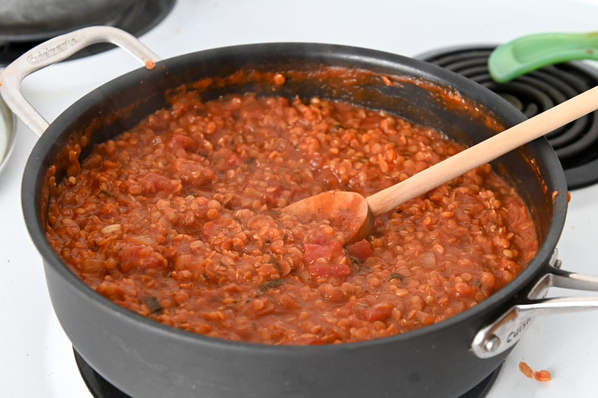 Thickened red lentil sauce in tall walled black sauce pan with a wooden spoon