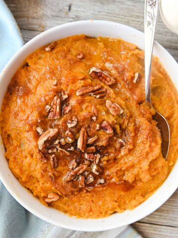Overhead view of white bowl filled with orange mashed sweet potatoes and pecans