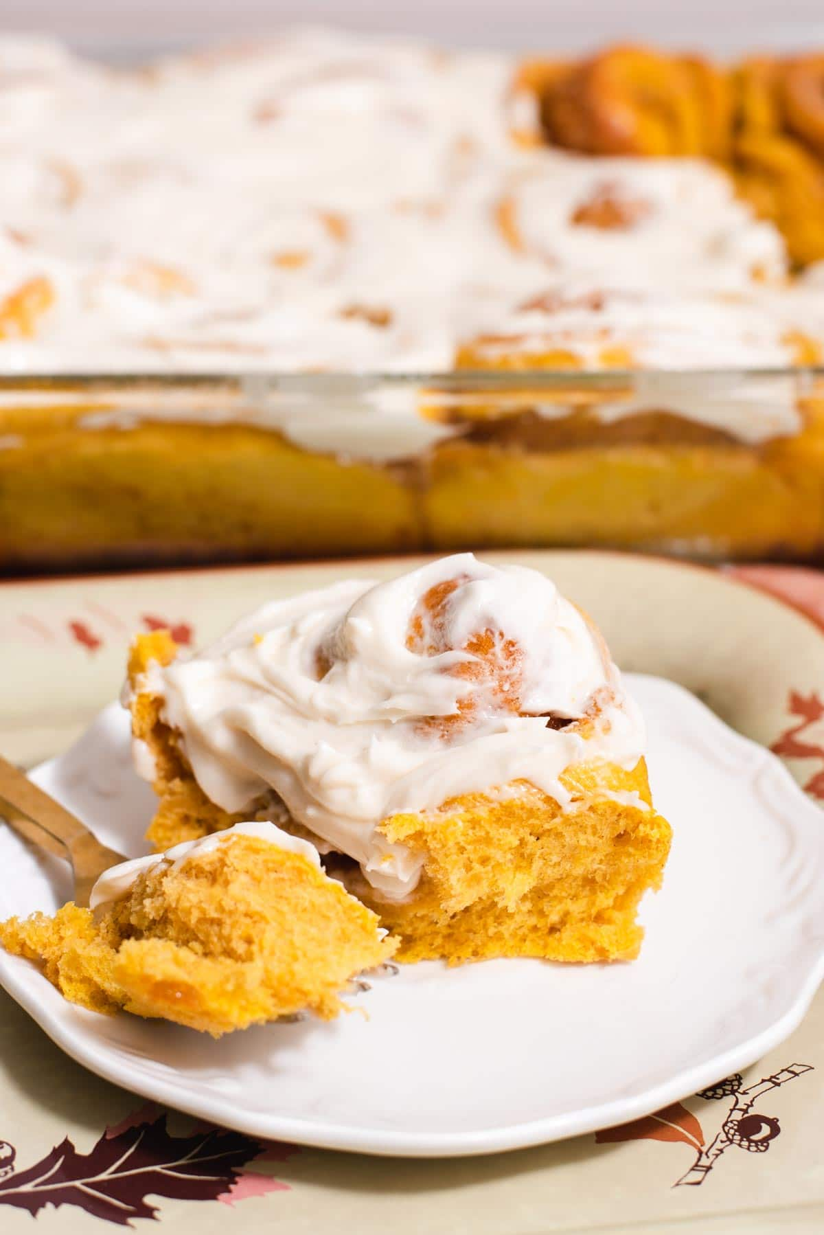 Single pumpkin cinnamon roll with white frosting on a white plate with more cinnamon rolls in the background