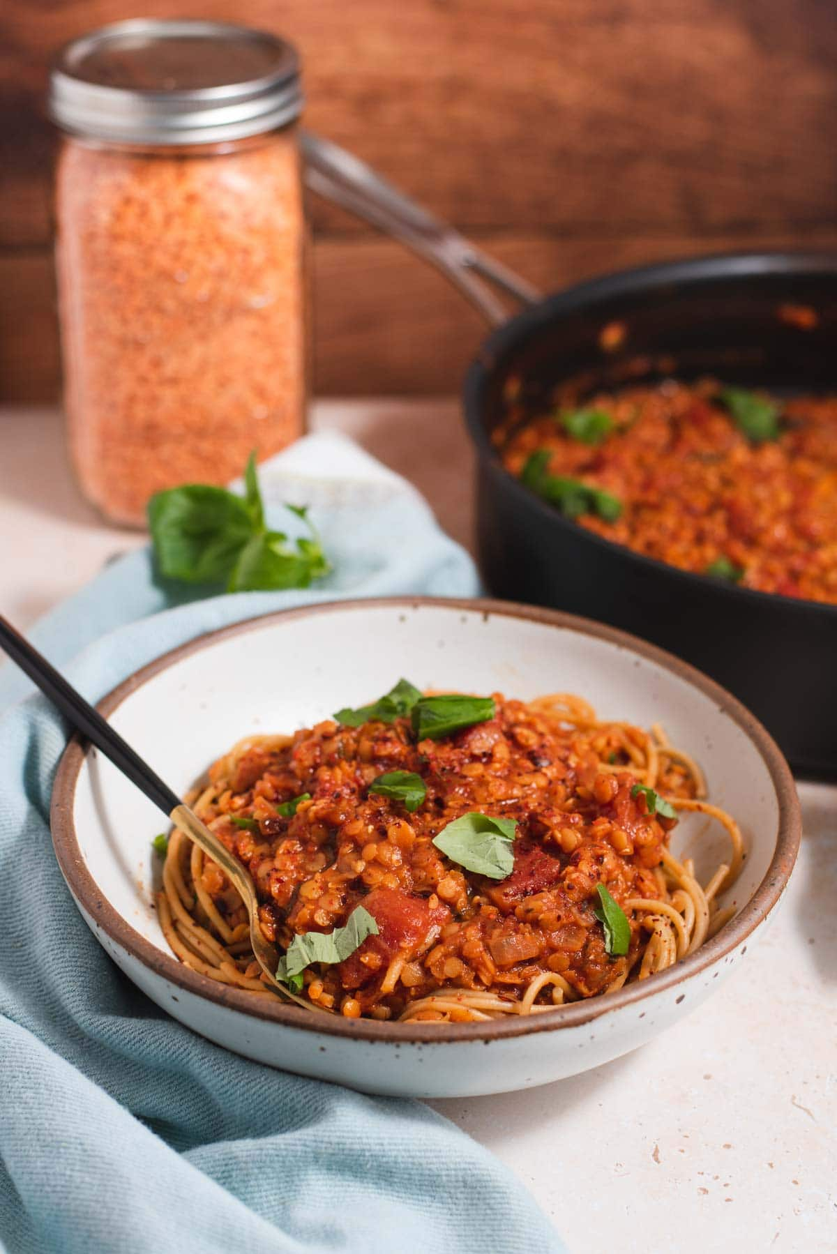 Side view of white bowl filled with spaghetti and a jar of red lentils in the background
