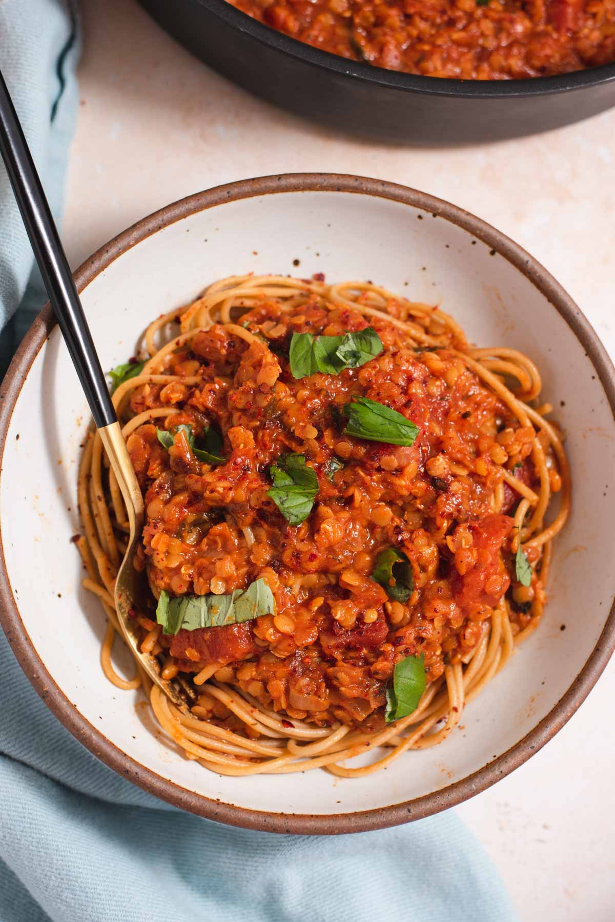 Spaghetti topped with red lentil tomato sauce and pieces of basil in a white bowl