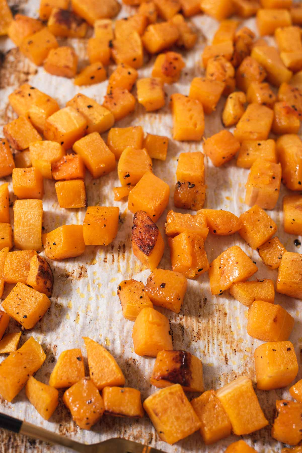 Golden roasted butternut squash on a piece of parchment paper