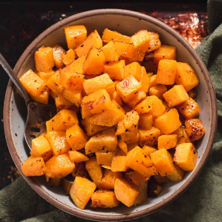Gray bowl filled with roasted butternut squash pieces next to a green cloth