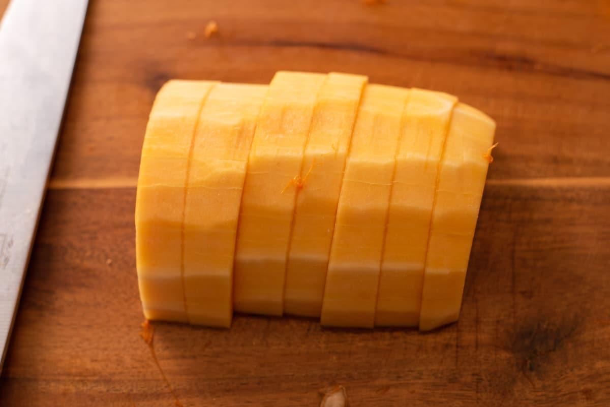Sliced butternut squash on a brown cutting board