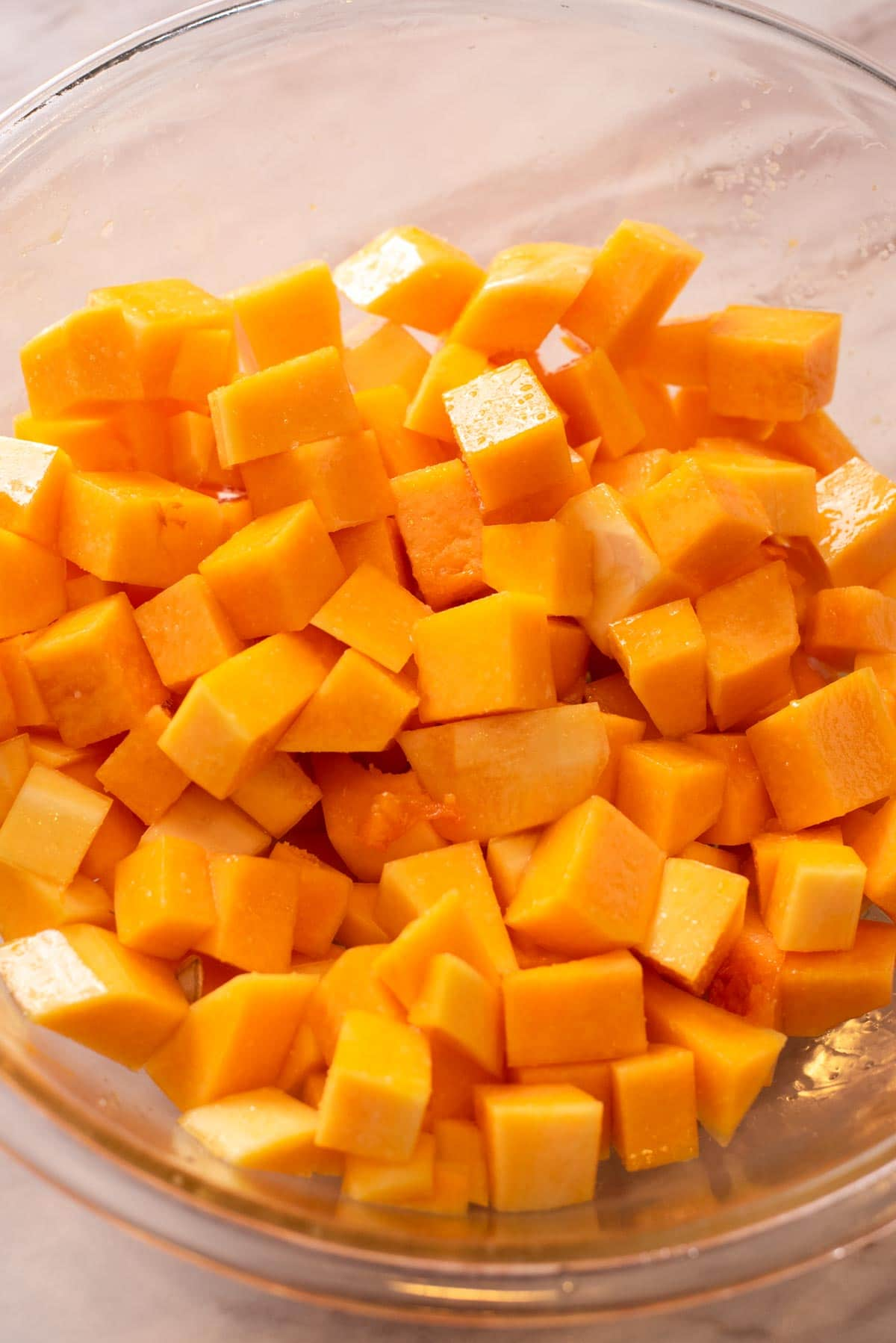 Diced butternut squash in a glass mixing bowl