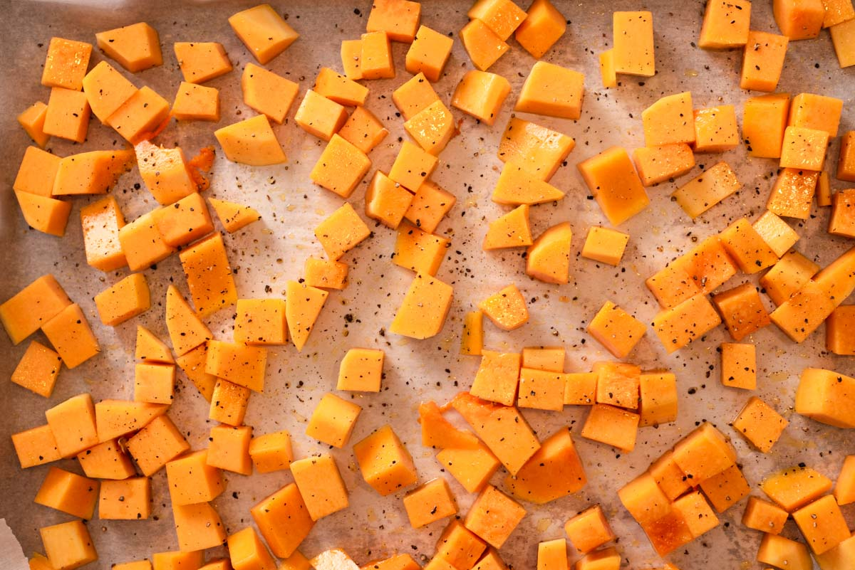Raw butternut squash pieces spread out on a parchment paper lined baking sheet