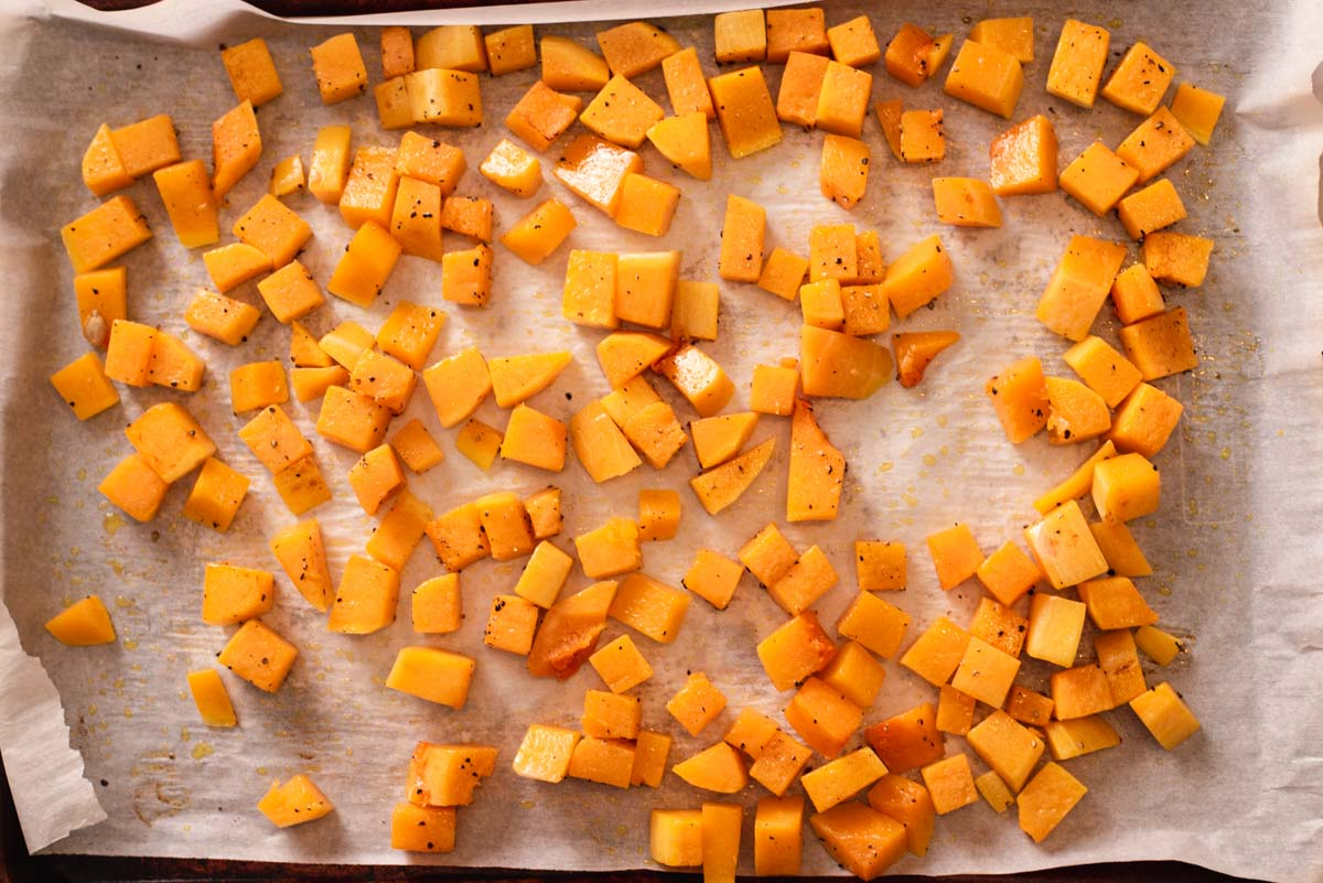 Slightly cooked butternut squash pieces on a parchment paper lined baking sheet