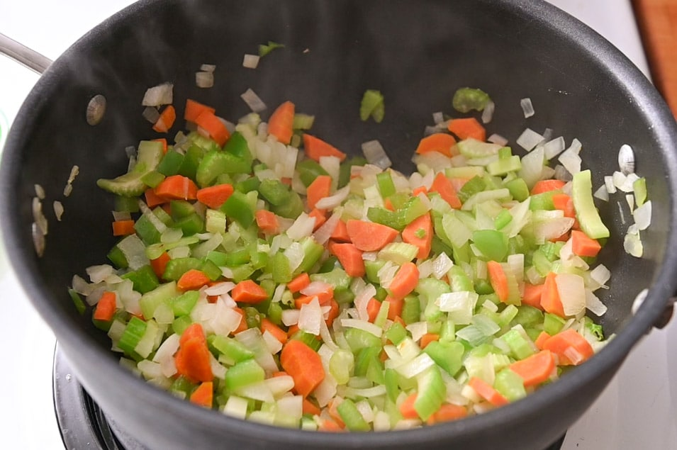 Onion, celery, carrot and bell pepper in a black Dutch oven