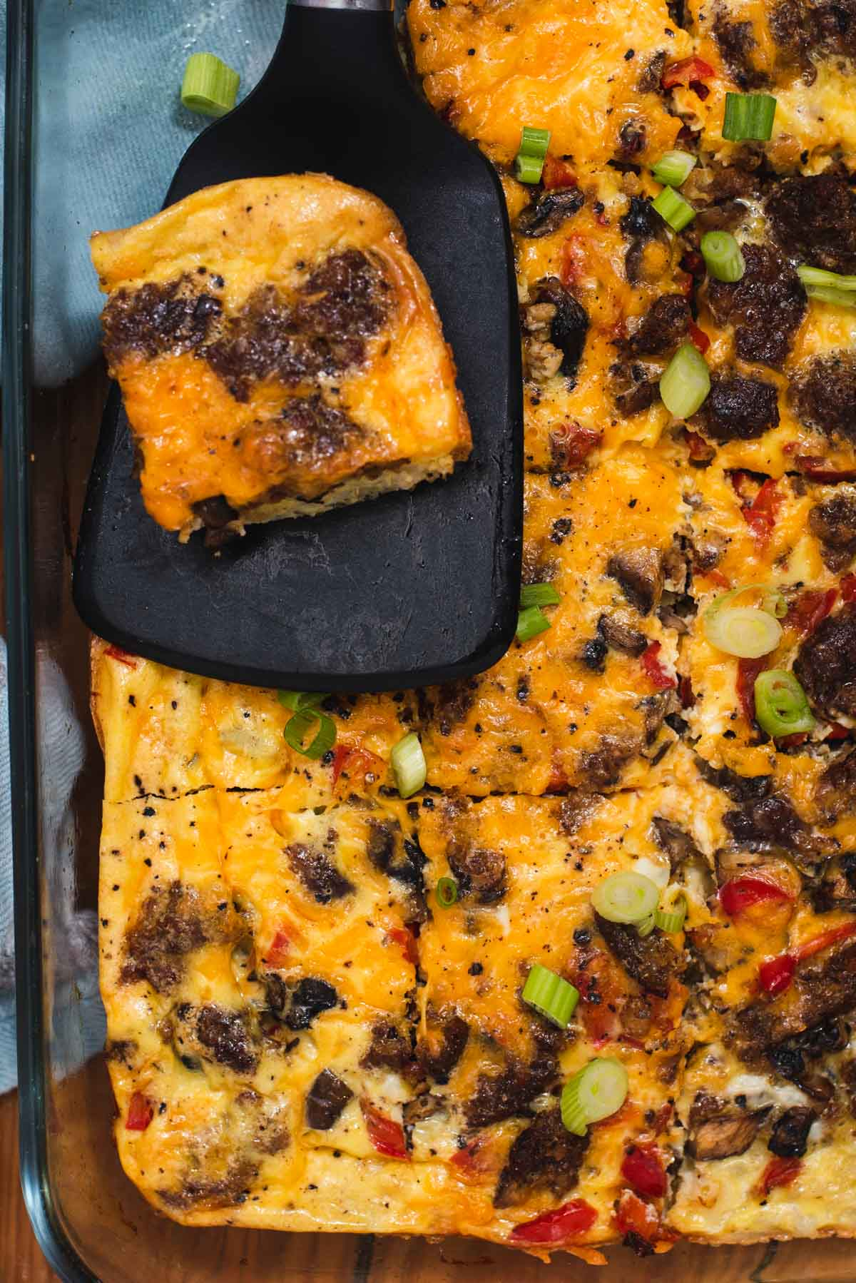 Overhead view of egg casserole with slice of egg casserole resting on a black spatula