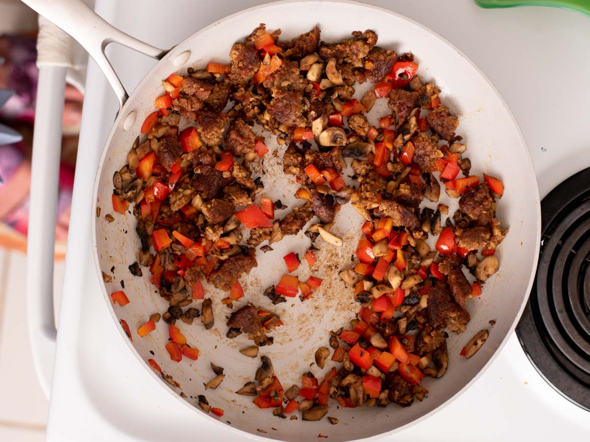 Crumbled veggie sausage, mushrooms and bell peppers in a skillet