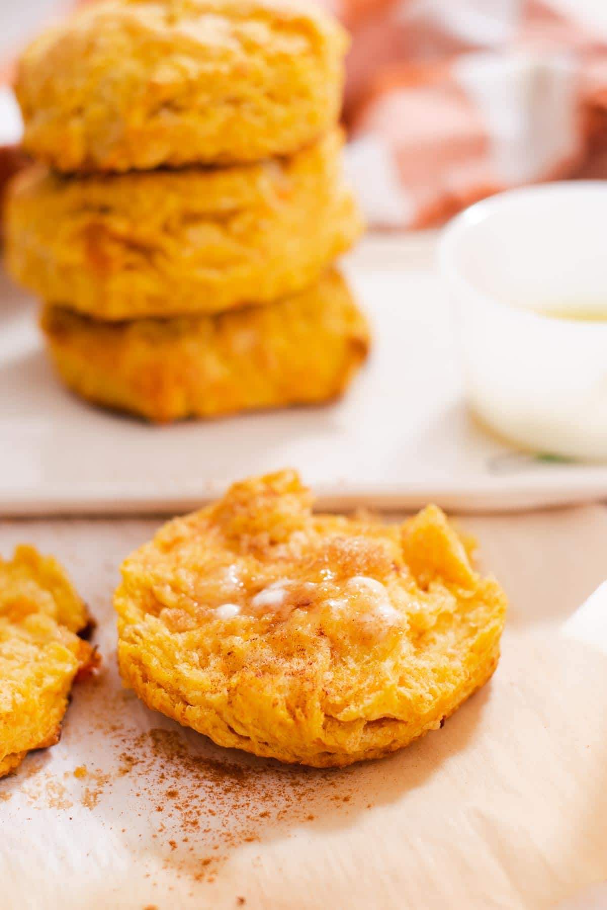 Half of a sweet potato biscuit topped with melted butter with more biscuits in the background